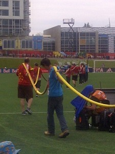 The hose team waters the artificial turf.